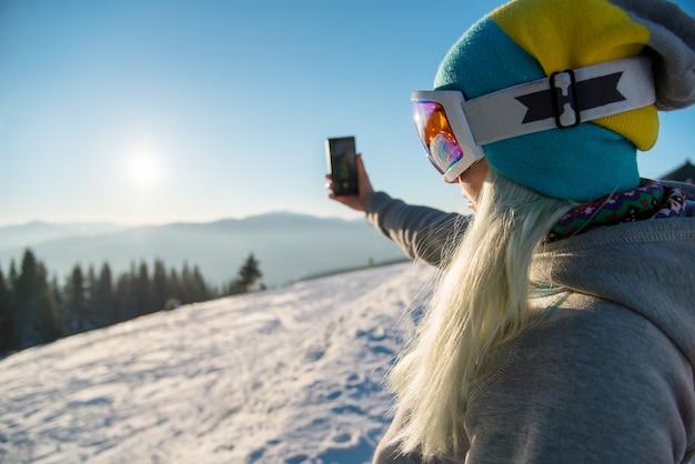 Snowboarder mit smartphone in den bergen