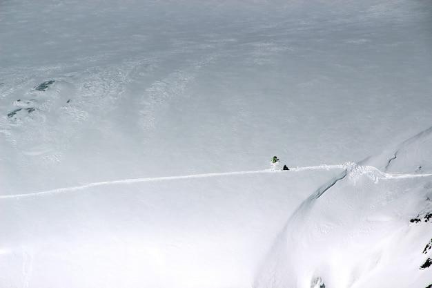 Snowboarder sitzen auf schnee an den hängen des berges elbrus kaukasus