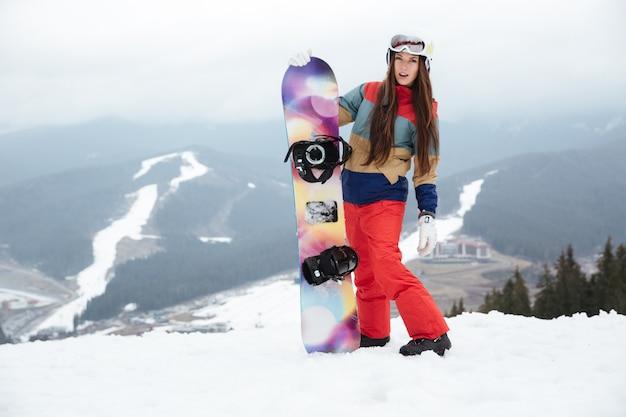 Snowboarderin der jungen dame auf den frostigen wintertagen der piste, die snowboard in den händen hält