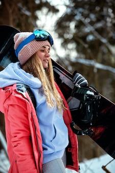 Snowboarderin im hellen anzug in einer sportbrille hält ein snowboard. extremsportarten. freizeit.