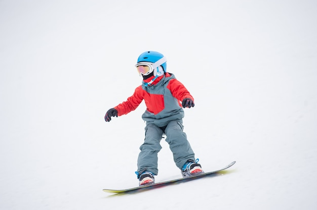 Snowboarderjunge, der über die steigung an den bergen reitet