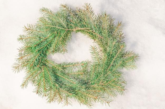 Snowy bereifter weihnachtskranz. kranz aus tannenzweigen auf schnee.
