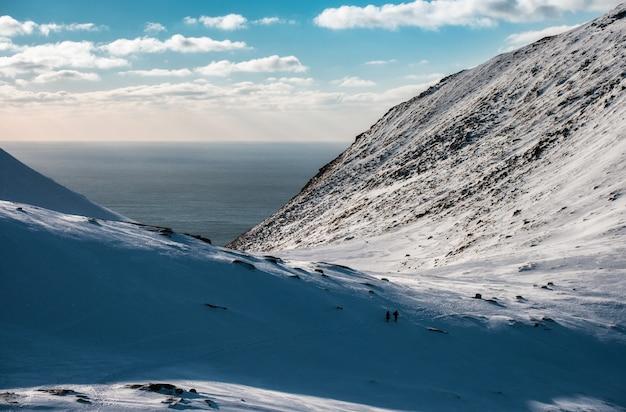 Snowy-steigungsberg auf arktischer küstenlinie