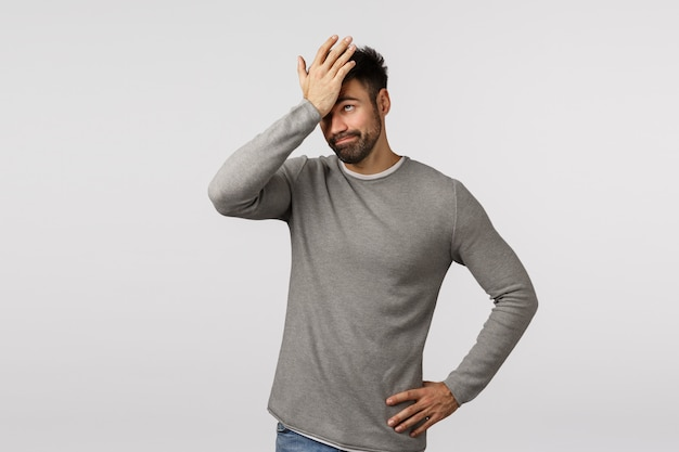 So dumm. vergesslicher und verärgerter, müder bärtiger mann in grauem pullover, gesichtspalme, schlag auf die stirn als vergessene wichtige aufgabe, lahme dumme idee hören, verärgert grinsen, verlegen stehen