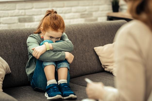 So einsam. deprimiertes freudloses mädchen, das ihre beine umarmt, während sie an ihre einsamkeit denkt