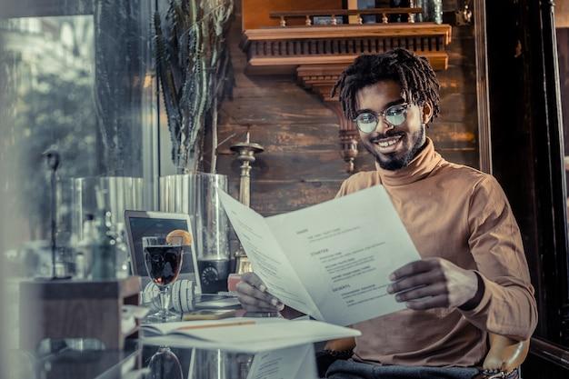 So erfreut. erfreuter junger mann, der ein lächeln auf seinem gesicht behält, während er informationen auf dokumenten liest
