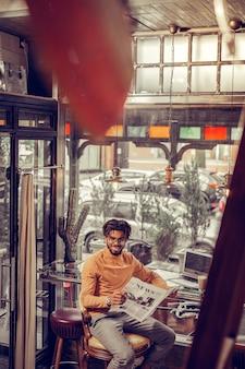 So erfreut. hübsche brünette männliche person, die lächeln auf seinem gesicht hält, während ruhe nach der arbeit hat