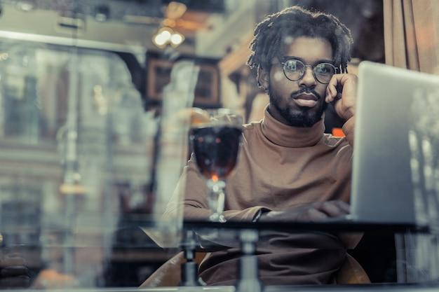 So ernst. konzentrierte männliche person, die lippen drückt, während sie bildschirm des laptops betrachtet