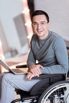 So glücklich. erfreuter behinderter mann, der lächeln auf seinem gesicht hält und auf rollstuhl sitzt