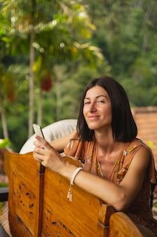 So hübsch. erfreute junge weibliche person, die ihr lächeln zeigt, während sie das telefon in beiden händen hält