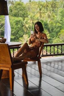 So hübsch. fröhliche junge weibliche person, die in der lounge-zone sitzt und mit ihrem freund plaudert