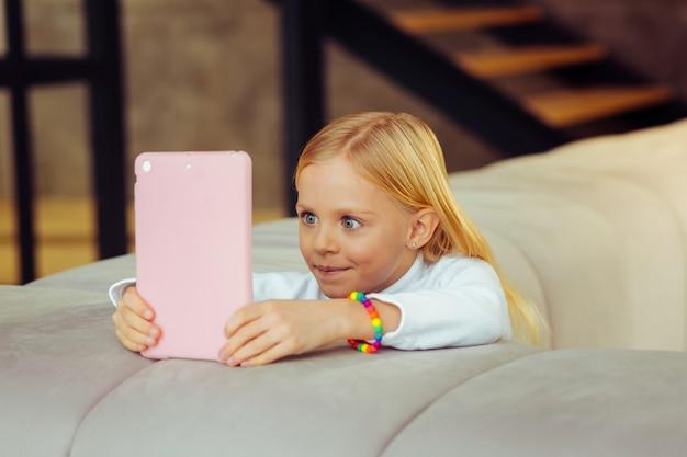 So interessant. aufmerksames mädchen, das positivität ausdrückt, während es auf den bildschirm ihres gadgets schaut