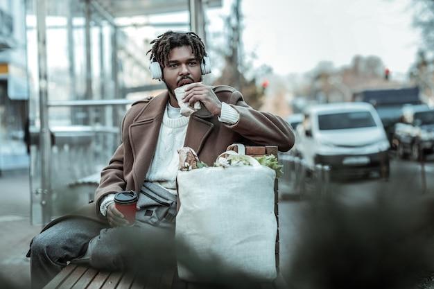 So lecker. fröhliche männliche person, die auf bank sitzt und pappbecher in der rechten hand hält