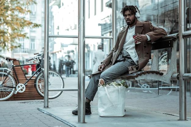So müde. erfreut bärtige männliche person, die pappbecher hält und auf seinen transport wartet