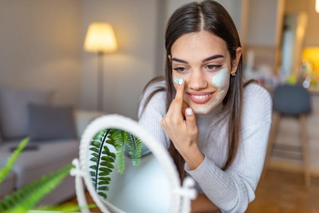 So schönes mädchen mit schönheitsmaske auf ihrem gesicht, das im spiegel schaut. schönheit, die zu hause natürliche selbst gemachte gesichtsmaske anwendet