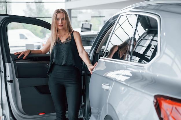 So sieht erfolg aus. mädchen und modernes auto im salon. tagsüber drinnen. neues fahrzeug kaufen