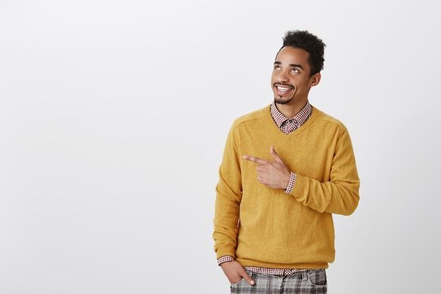 So sieht zufriedenheit aus. erfreut über einen glücklichen, charmanten, dunkelhäutigen mann mit afro-haarschnitt, der mit dem zeigefinger nach links zeigt, zum himmel aufblickt, einen guten tag genießt und einen schönen ort zum trinken vorschlägt