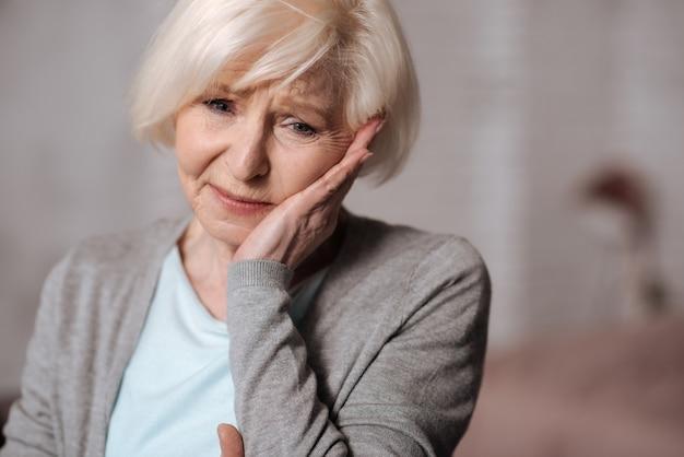 So unerwartet. schließen sie herauf porträt der sehr depressiven älteren dame, die ihren cheeck mit hand berührt.