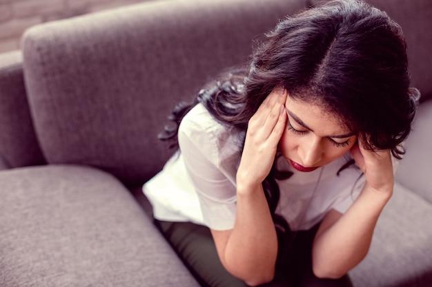So verärgert. unglückliche freudlose frau, die ihre schläfen berührt, während sie sich sehr verärgert fühlt