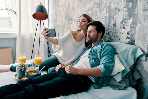 So viel spaß! schönes junges paar, das selfie macht und gesichter macht, während es zeit im bett zu hause verbringt