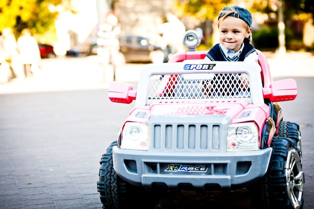 So wenig und so großer junge. kind sieht mutig aus, seinen spielzeugausländer zu fahren