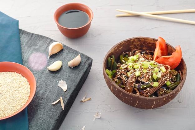 Soba mit pilzen und grünen bohnen mit sesam in einer platte der kokosnussschale auf einem grauen betonhintergrund. horizontales foto