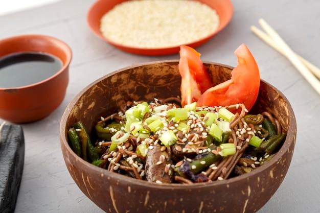 Soba mit pilzen und grünen bohnen mit sesam in einer platte der kokosnussschale auf einem grauen betonhintergrund nahe knoblauch und sojasauce. horizontales foto