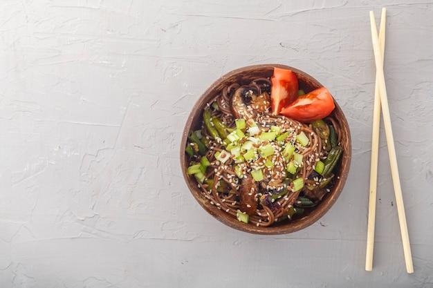 Soba mit pilzen und sesam in einer schüssel kokosnussschalen auf einem konkreten hintergrund nahe stöcken. horizontales foto