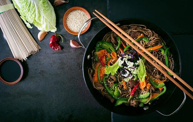Soba-nudeln mit rindfleisch, karotten, zwiebeln und paprika