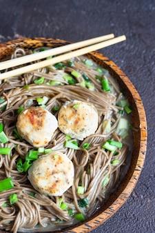 Soba-nudeln, serviert mit hühnerfleischbällchen und frühlingszwiebeln.