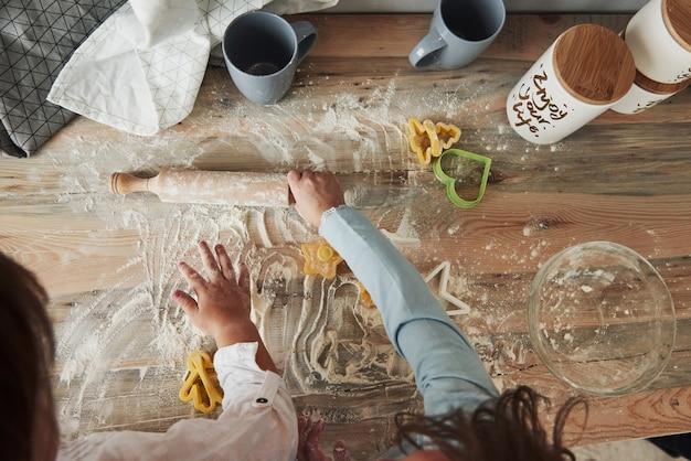 Sobald sie große köche werden. jetzt einfach spaß haben. draufsicht auf kinder, die lernen, mit speziell geformten instrumenten essen aus dem mehl zuzubereiten.