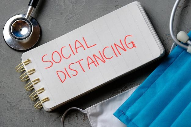Social distancing zitat auf kleinem notizbuch. das konzept der gesundheitsversorgung und medizin inmitten einer corona-virus-pandemie