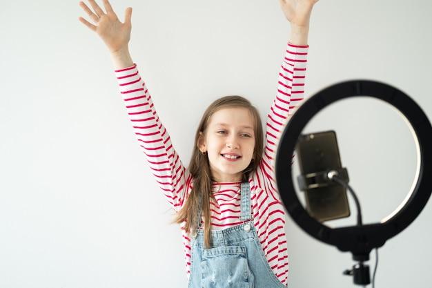 Social-media-bloggerin im teenageralter, die videoaufnahmen aufnimmt und das smartphone auf einem stativ mit ringlicht betrachtet.