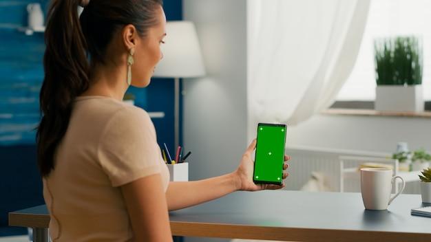 Social-media-frau mit touchscreen-telefon mit mock-up-chroma-schlüssel auf grünem bildschirm, der am modernen schreibtisch sitzt. kaukasische frau, die an einer online-app mit smartphone mit isoliertem display arbeitet