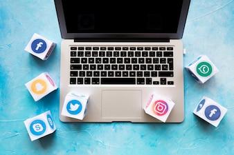 Social Media-Ikone blockiert auf Laptop über dem blauen Hintergrund