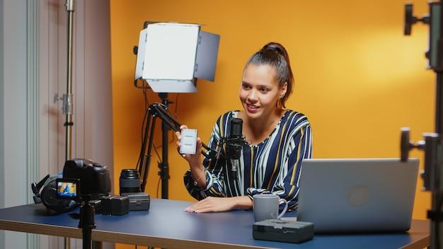 Social-media-influencer, der im professionellen studio eine mini-led-light-rezension durchführt. video-blogger, der einen vlog mit technologischen produktgeräten aufzeichnet, die in der videografie und fotografie verwendet werden
