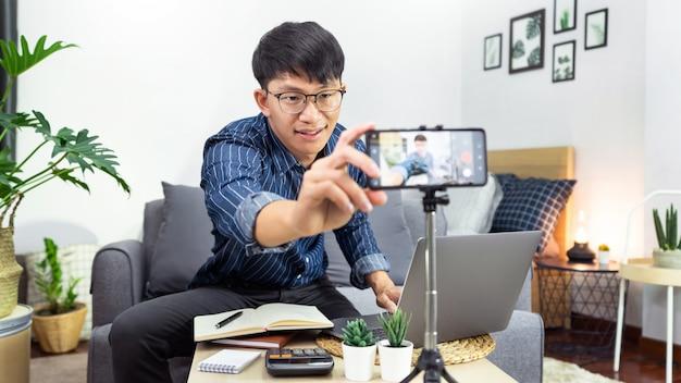 Social-media-influencer oder blogger präsentieren und überprüfen die aufzeichnung oder das streaming von vlogs über produkte mit dem smartphone auf einem stativ für social-media-kanäle, die ein live-stream-konzept erstellen.