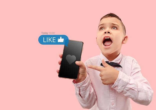 Social-media-interaktionen auf dem handy. digitales internetmarketing, chatten, kommentieren, liken. lächeln und symbole über dem smartphone-bildschirm, die von einem kleinen jungen auf korallenstudio-hintergrund gehalten werden.