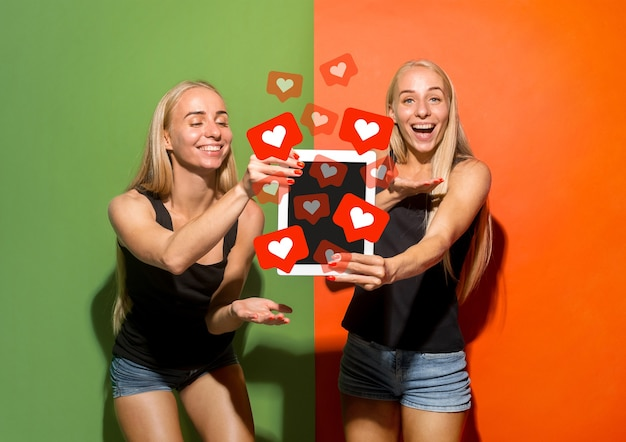 Social-media-interaktionen auf dem handy. digitales internetmarketing, chatten, kommentieren, liken. lächeln und symbole über dem smartphone-bildschirm, die von jungen frauen auf hellem studiohintergrund gehalten werden.
