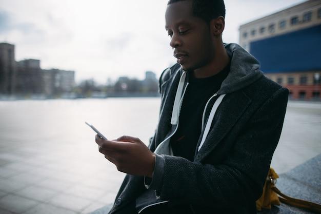 Social-media-kommunikation. nachdenklicher schwarzer mann, der auf smartphone plaudert. moderner lebensstil, streetstyle, junger mann im selektiven fokus, technologiekonzept