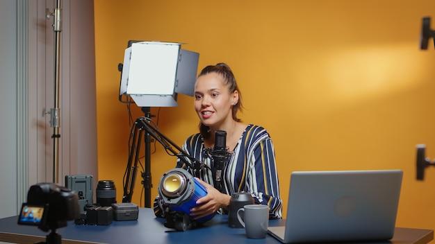 Social-media-star-aufnahme von kameraeindrücken von videoleuchten im professionellen studio. influencer für neue medien, der online interessante inhalte über professionelle videoausrüstung für web-abonnenten erstellt und