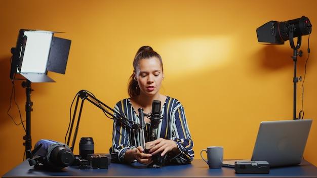 Social-media-star präsentiert in ihrem professionellen studio einen flüssigen stativkopf. influencer, der online-internetinhalte über videogeräte für web-abonnenten und -vertrieb erstellt, digitaler vlog