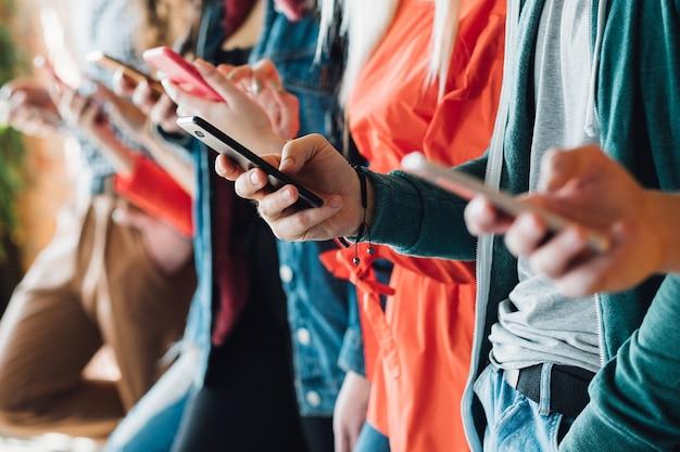 Social-media-sucht. rudern sie leute mit smartphones. lebensstil der millennials. technik freizeit.