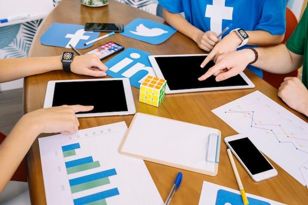 Social media-team, das digitale tablette mit social media-ikonen auf schreibtisch verwendet
