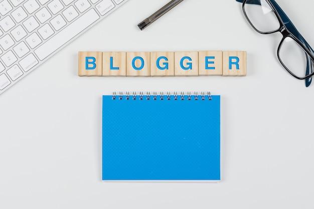 Social media und geschäftskonzept mit holzklötzen, notizbuch, brille, stift, tastatur auf weißem hintergrund flach legen.