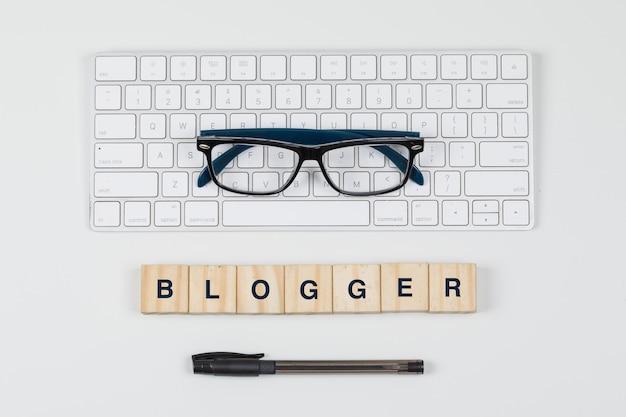 Social media und geschäftskonzept mit holzklötzen, tastatur, brille, stift auf weißem hintergrund flach liegen.