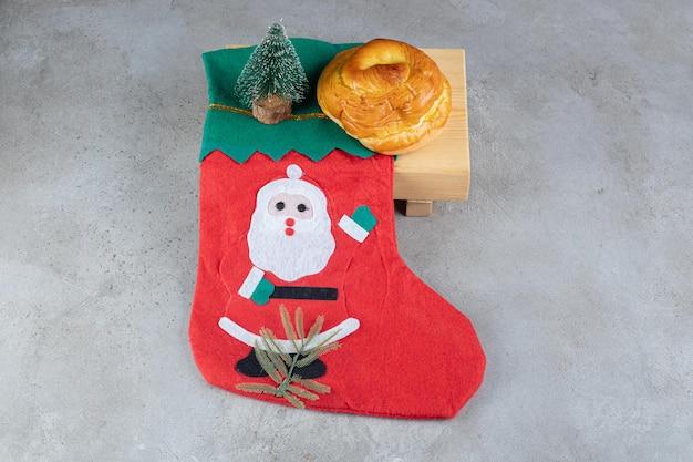 Socke mit weihnachtsmannillustration, süßem brötchen und einer kleinen baumfigur auf marmortisch.