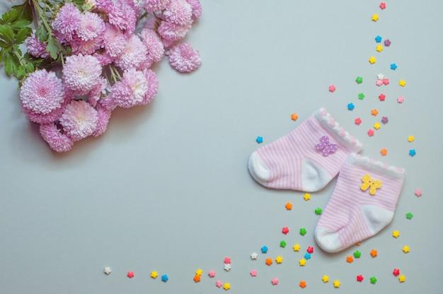 Socken und chrysanthemenblüten auf grau