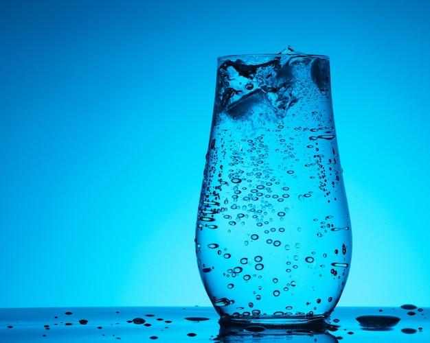 Soda mineralwasser in glas mit eis, blasen und tröpfchen auf dem blauen gradientenhintergrund, konzept der gesundheit und frische
