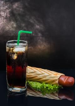 Soda mit eis und schweinen in einer decke hot dog auf grünem salat über dunklem reflektierendem hintergrund. dampf im hintergrund.